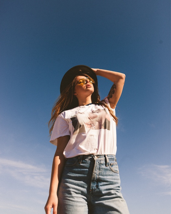 woman wearing white t-shirt and jeans stands in front of a blue sky
