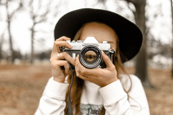 woman wearing a black hat takes a photo with a vintage camera