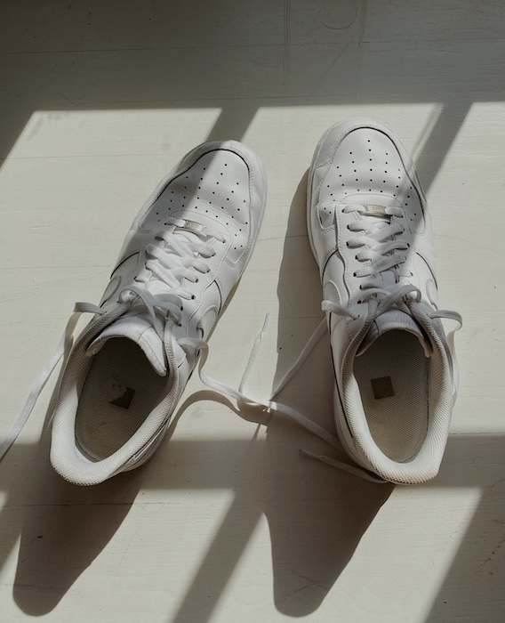 white sneakers on a white surface with shadows cast over them