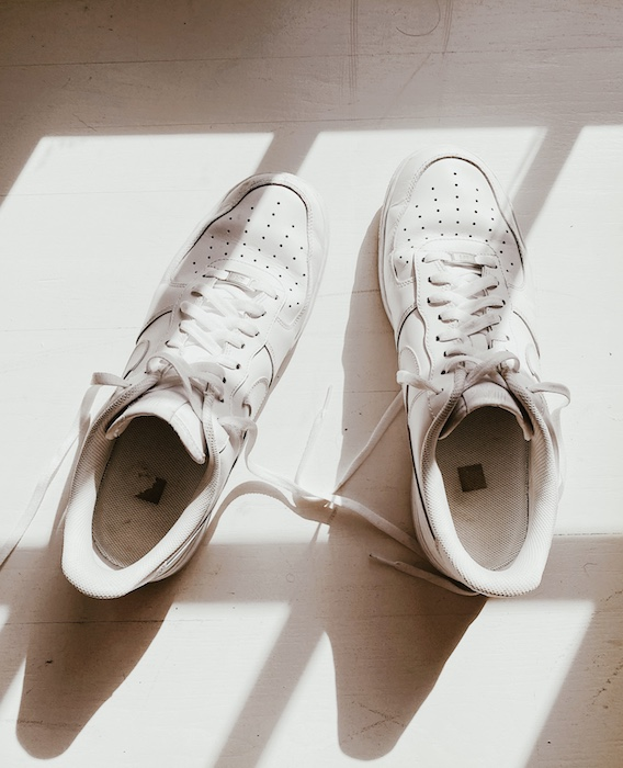 brightly lit photo of white sneakers on a white surface