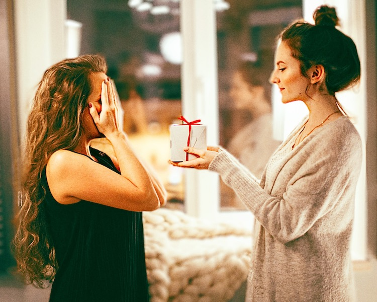 woman covers her eyes while another woman surprises her with a gift
