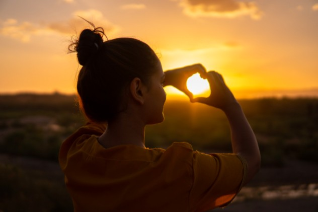 Una imagen de una niña con el pelo lacio, atada en un moño. Haciendo un corazón con sus manos, en vista de una puesta de sol en la montaña.