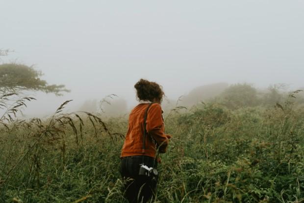 Una imagen de una joven de pelo rizado, vestida con un cárdigan naranja, caminando en medio de un campo con una cámara fotográfica.