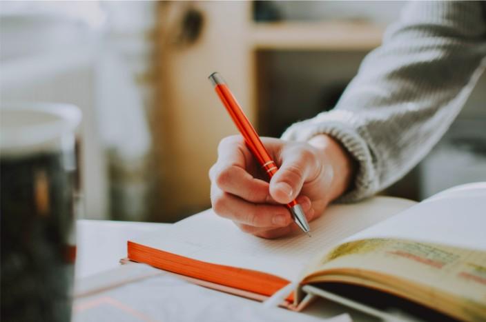 Una imagen de una persona que escribe en un cuaderno con un bolígrafo rojo.
