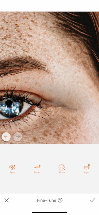 Picture of a white woman with freckles being edited by AirBrush with Fine-tune tool