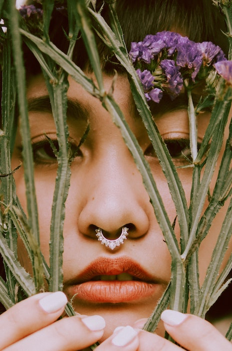 Picture of a woman with flowers close to her face