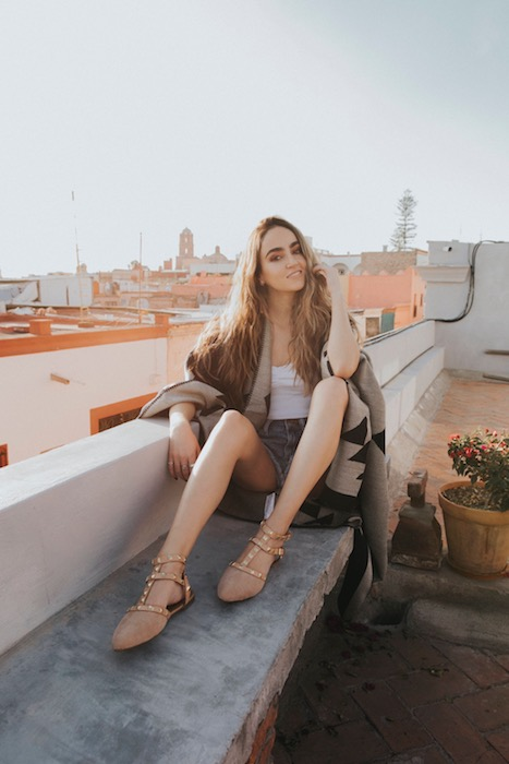 woman sitting on a rooftop overlooking the city