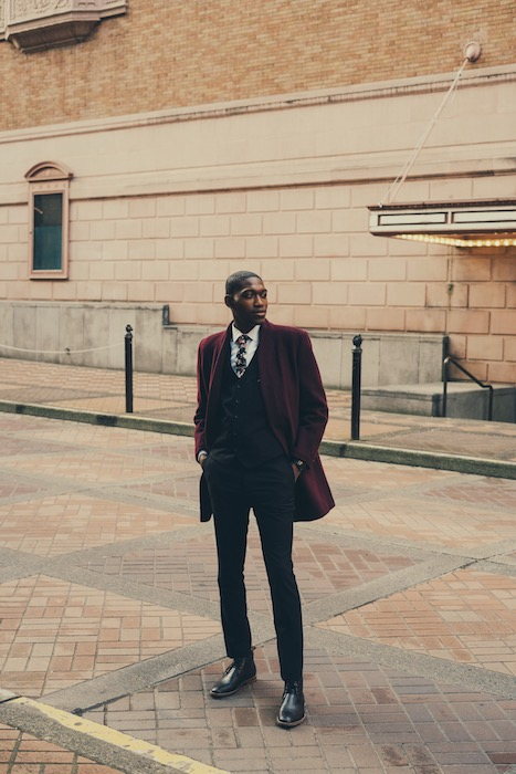 man wearing a suit standing on the sidewalk