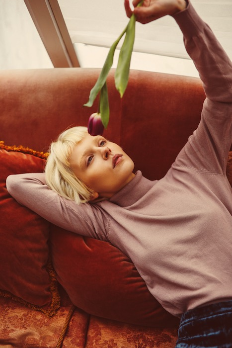 woman wearing a pink sweater lying on a sofa holding a flower