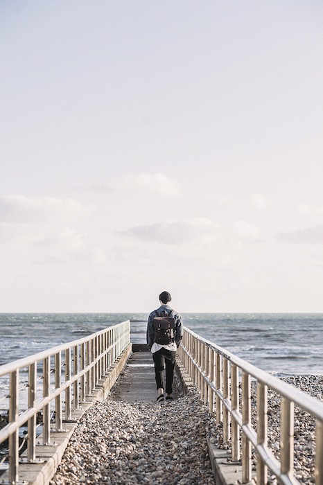 man with a backpack walking along a jetty