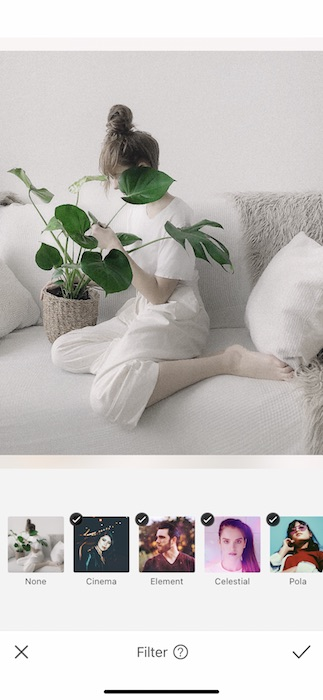 black and white photo of a woman sitting on a white couch holding a plant