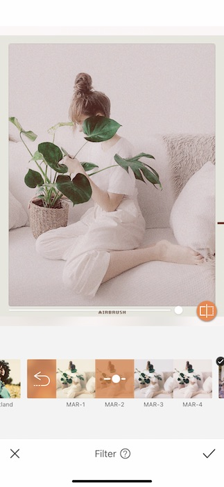 woman sitting on a white couch holding a plant