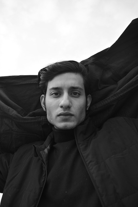 black and white photo of man with dark hair in front of black and white background