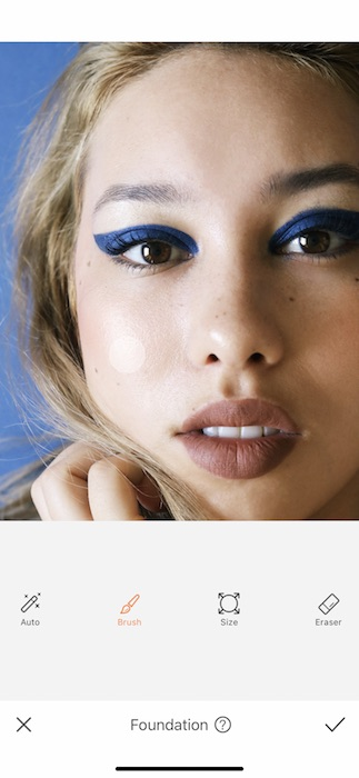 closeup of woman with blonde hair and blue eyeliner in front black background