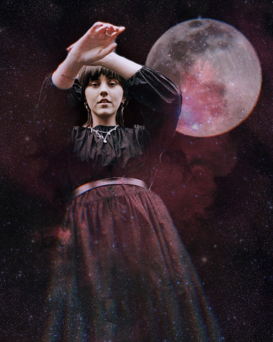 woman wearing a black dress standing in front of the moon