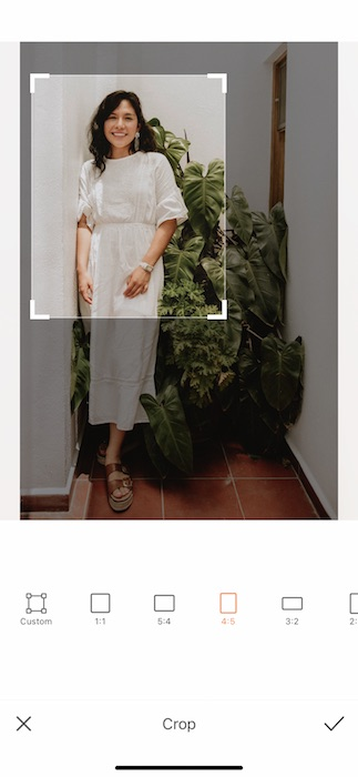 woman in a white dress standing in front of a green plant