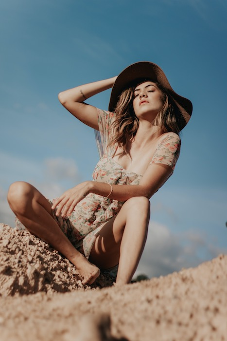 woman wearing a hat sitting in sand