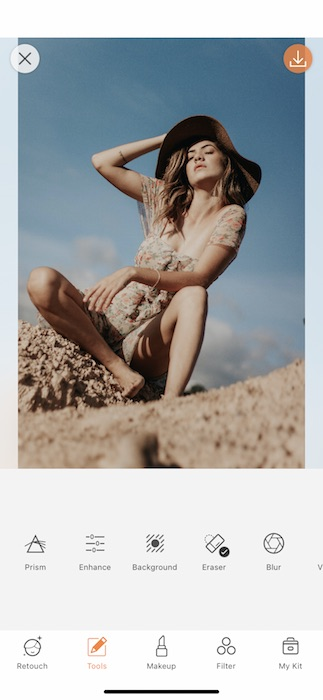 woman wearing a hat and floral dress sitting in the desert