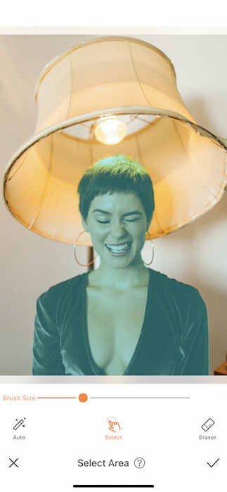 woman with a pixie haircut making a silly face while sitting under a lamp