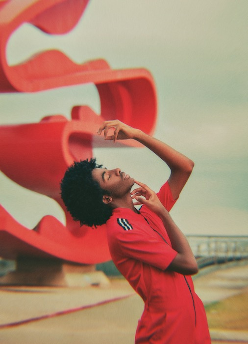black man in red jumpsuit in front of curvy red sculpture