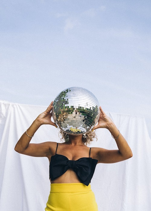 woman in yellow skirt holding disco ball with sky background