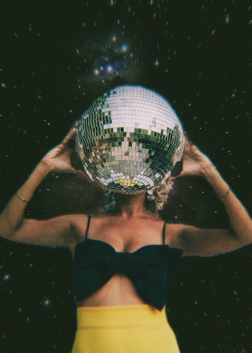 woman in yellow skirt holding disco ball in front of starry background