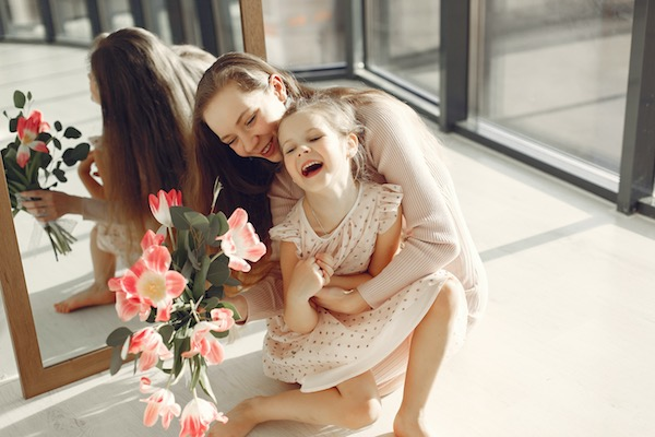 mother hugging toddler daughter and laughing