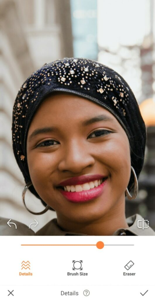 closeup of black woman wearing black head scarf and pink lipstick