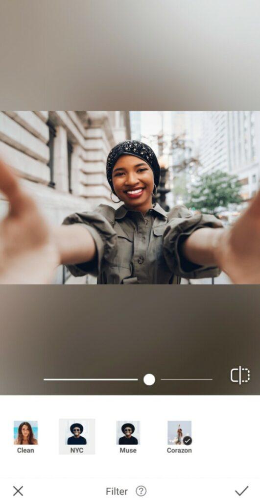 black woman wearing black head scarf taking a selfie in the city