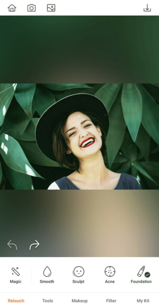 laughing woman wearing a hat in front of a leafy background