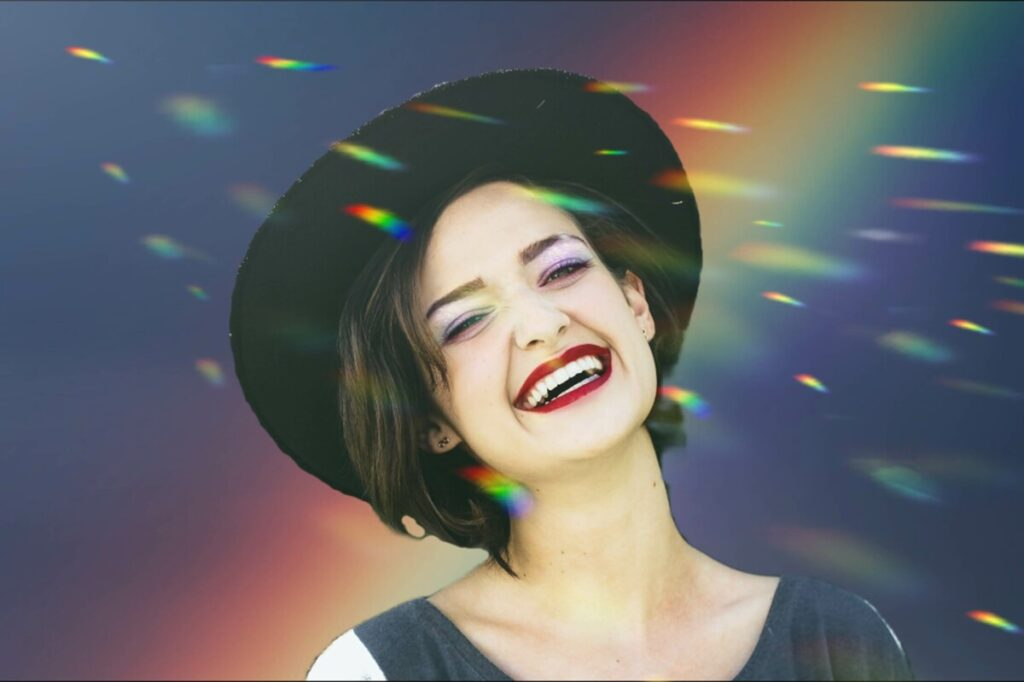 Pride edit of laughing woman wearing a hat in front of a rainbow background