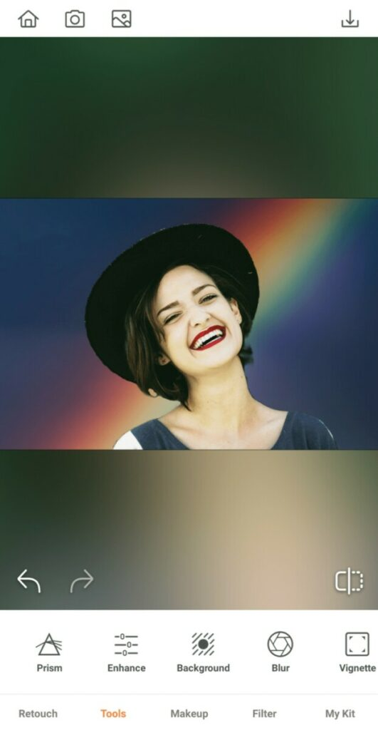 laughing woman wearing a hat in front of a rainbow background