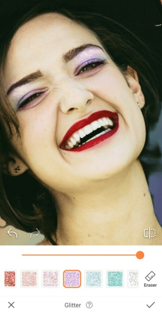 closeup of a laughing woman with red lipstick and glitter on her eyelids for Pride edit