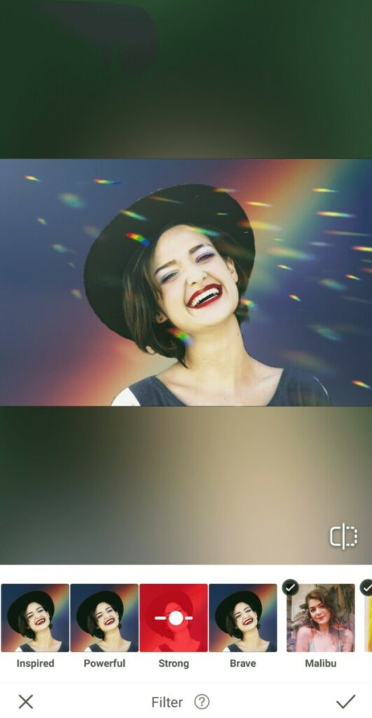 Pride edit of laughing woman wearing a hat in front of a rainbow background with light flares