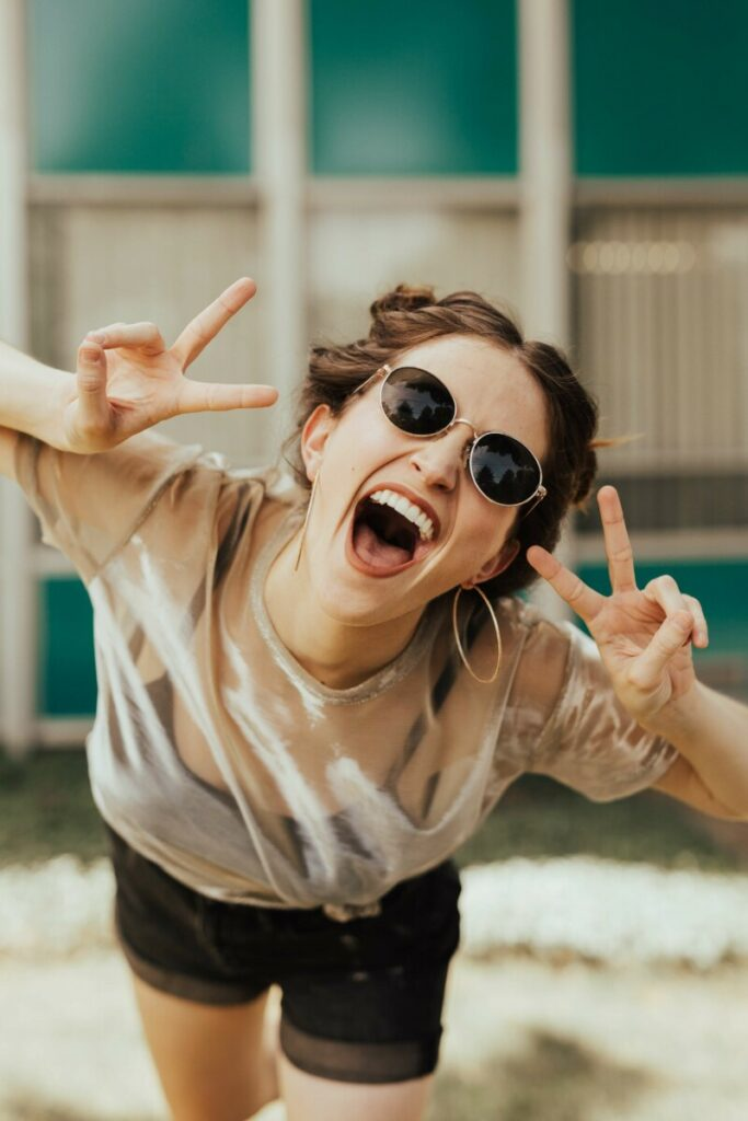 laughing woman in white top and sunglasses making the peace sign