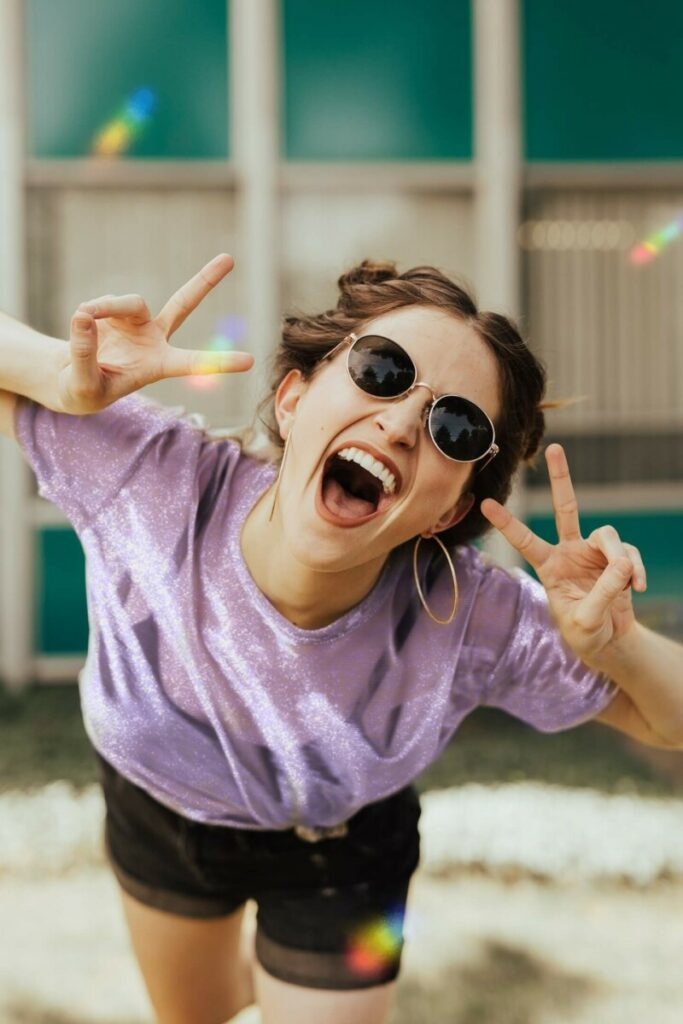 Pride Month edit of laughing woman in purple top and sunglasses making the peace sign