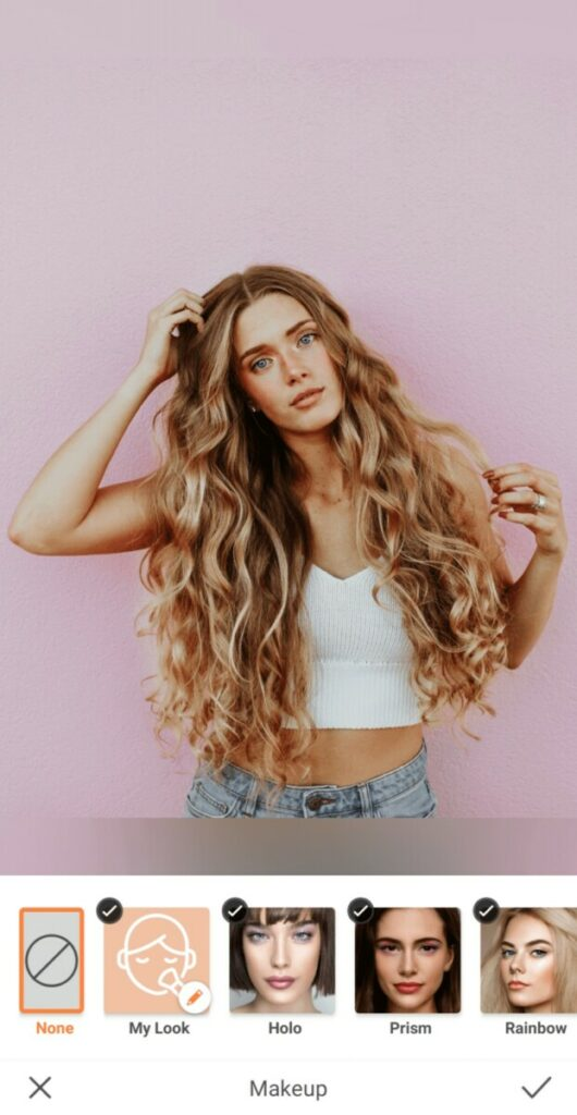 woman with curly blonde hair standing in front of a pink wall