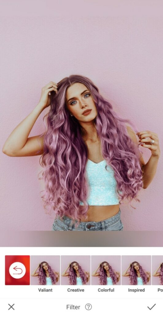 Pride edit of woman with purple hair in a white top stands in front of a pink wall