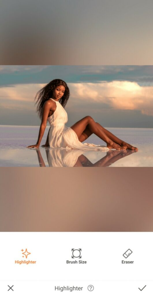 International Day of Tropics edit featuring woman in a white dress sitting in water against a sunset sky