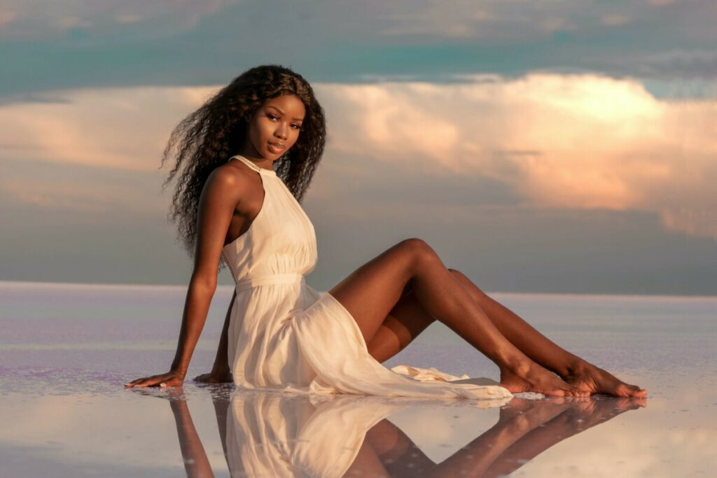 woman in a white dress sitting in water against a sunset sky