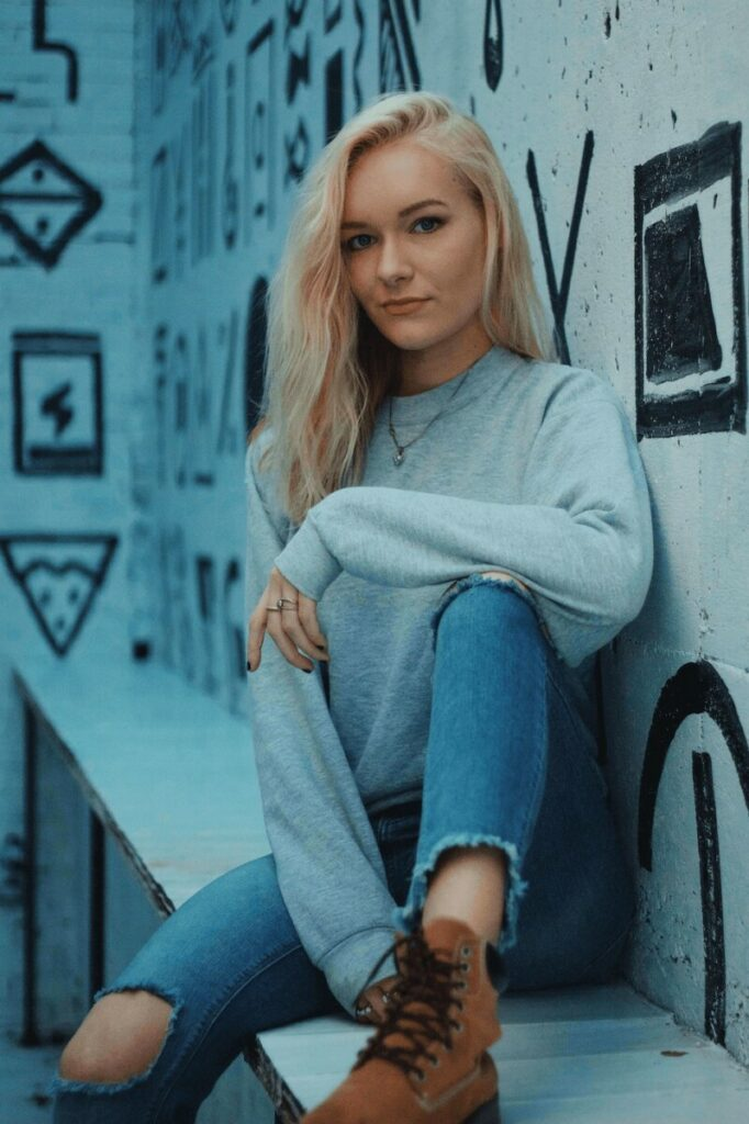woman in grey sweater and jeans sitting in front of black and white mural