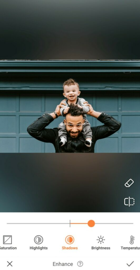 dad holding his toddler son on his shoulders in front of green garage wall