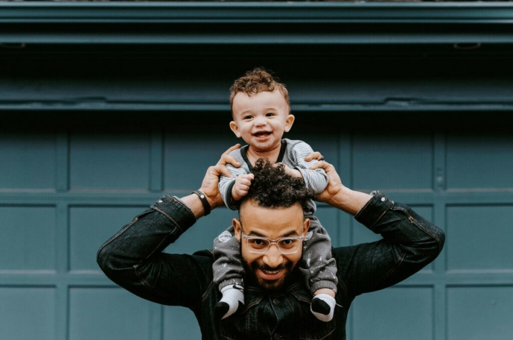 father holding his toddler son on his shoulders in front of green garage wall