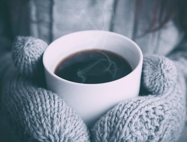 Uma caneca branca de café sendo segurada por mãos protegidas por luvas de tricô de cor cinza