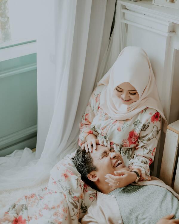 Homem sorridente deitado com a cabeça no colo da mulher que também está sorrindo