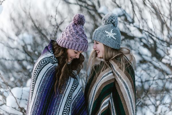 Duas amigas enroladas em cobertores