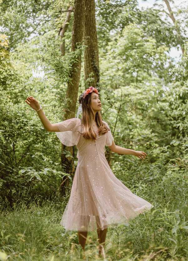 Garota com vestido rosa esvoaçante em uma floresta