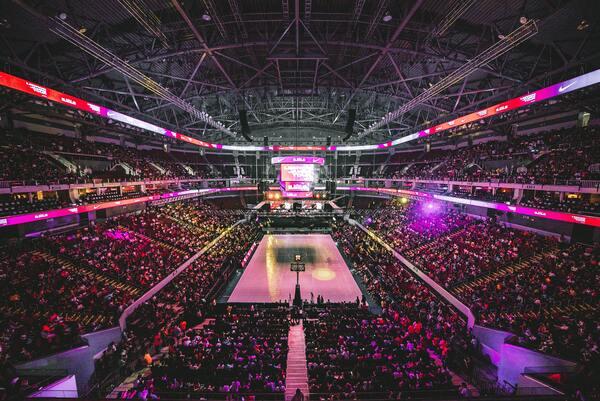 Estádio de basquete com arquibancadas lotadas de pessoas.