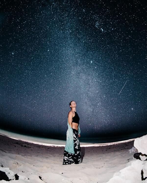 Garota de blusa preta e saia estampada com um céu estrelado ao fundo