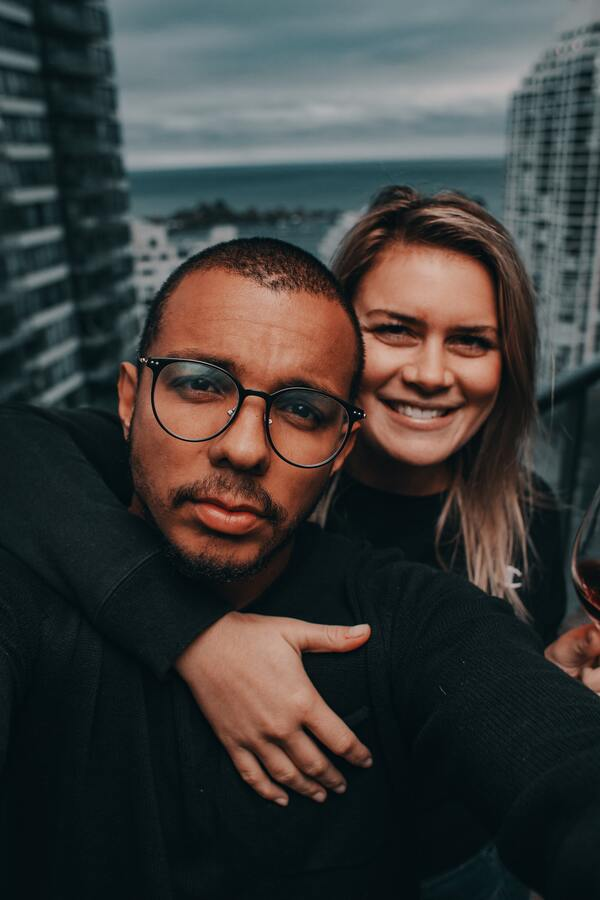 Homem de camisa preta com uma mulher abraçando-o